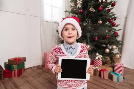 Foto de Habitación decorada en chico lindo en sombrero de santa con tableta en Navidad - Imagen libre de derechos
