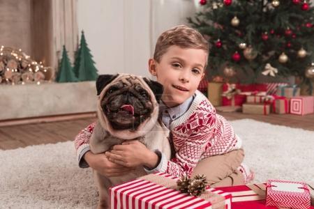 chico abrazando pug en Navidad