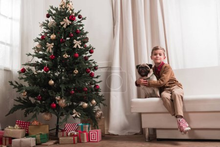 boy sitting on couch with pug