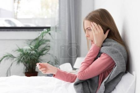 Photo for Shocked girl looking on thermometer and lying in bed at home - Royalty Free Image