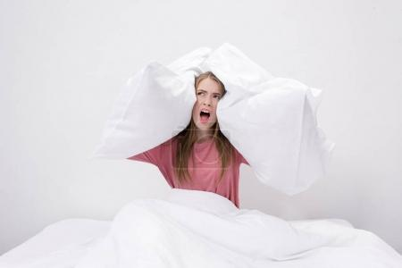 Photo for Angry woman with insomnia yelling and holding pillows while sitting in bed - Royalty Free Image