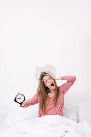 Photo for Young sleepy woman yawning and holding alarm clock, in bed in the morning - Royalty Free Image