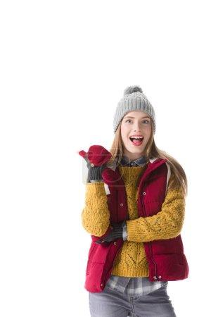 Photo pour Femme excitée dans les vêtements d'hiver pointant sur quelque chose, isolé sur blanc - image libre de droit