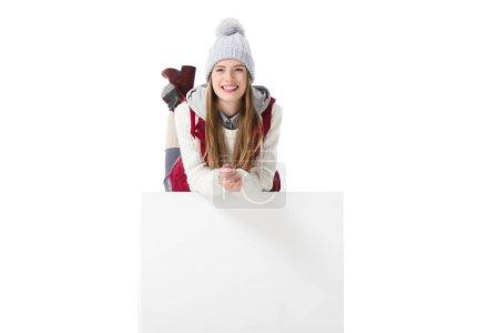 Photo pour Jolie fille souriante en vêtements d'hiver couché sur cube blanc, isolé sur blanc - image libre de droit