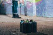 """Постер, картина, фотообои """"низкая часть уличного художника граффити живопись ночью, банок с аэрозольной краской на переднем плане"""""""