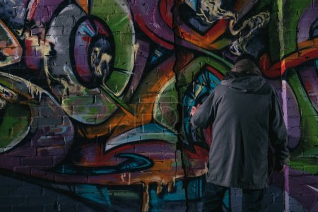 back view of street artist painting graffiti with aerosol paint on wall at night