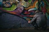 """Постер, картина, фотообои """"вид сзади уличного художника граффити картины с аэрозольной краской на стене в ночное время"""""""