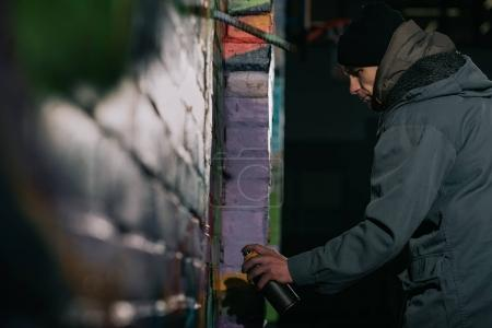 Photo for Street artist painting graffiti with aerosol paint on wall at night - Royalty Free Image
