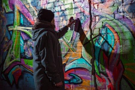 artiste de rue peinture graffiti avec peinture aérosol sur le mur la nuit