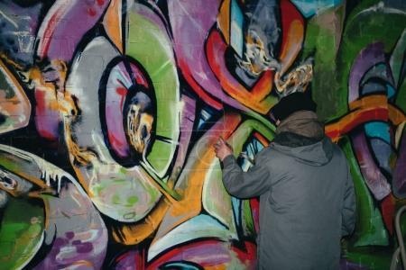 Photo pour Vue arrière du graffiti peinture artiste de rue avec de la peinture aérosol sur mur pendant la nuit - image libre de droit