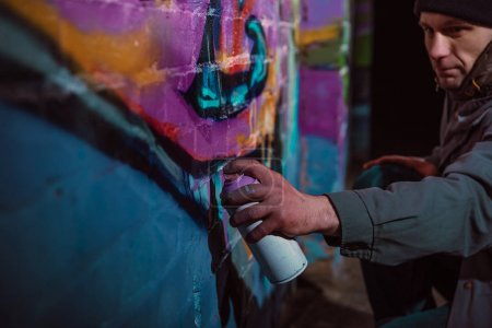 man painting graffiti with aerosol paint on wall at night