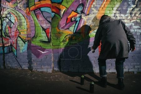 vista trasera del artista callejero pintando graffiti con pintura en aerosol en la pared por la noche