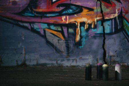 colorful graffiti on wall cans with aerosol paint standing on foreground
