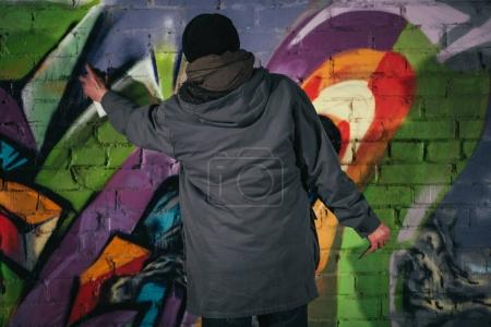 back view of man painting graffiti with aerosol paint on wall at night