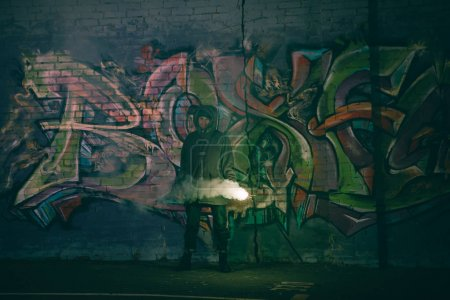 Photo for Person holding smoke bomb and standing against wall with graffiti at night - Royalty Free Image