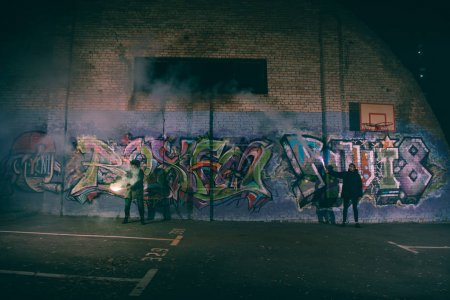 Photo for People holding smoke bombs and standing against wall with graffiti at night - Royalty Free Image