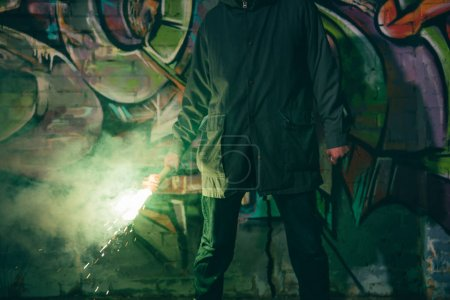 Photo for Cropped view of man holding smoke bomb and standing against wall with graffiti at night - Royalty Free Image