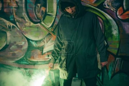 Photo for Caucasian man holding smoke bomb and standing against wall with graffiti at night - Royalty Free Image