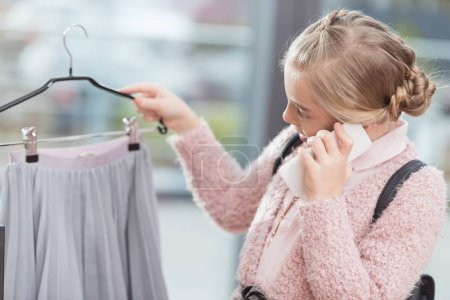 child speaking on smartphone while holding cloth on hanger in hand at shop
