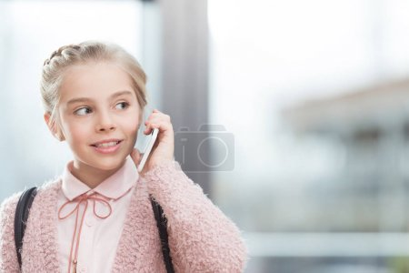 child speaking on smartphone against window during daytime