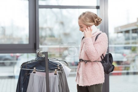 caucasian child speaking on smartphone while standing near cloth hanger at shop