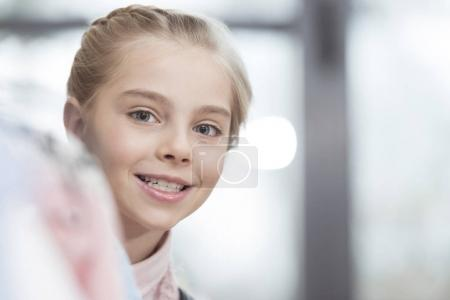 happy child looking out from row of clothes on hanger at shop
