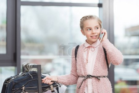 caucasian child using smartphone while standing near cloth hanger at shop