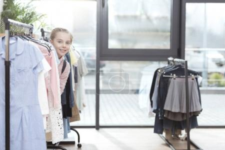 smiling kid looking out from row of clothes on hanger at shop