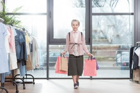 smiling kid holding paper shoping bags in hands while standing surrounded by hangers at shop
