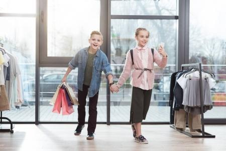 happy children with shopping bags making selfie at shop