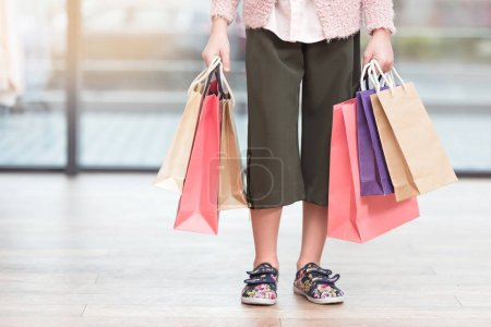 cropped image of  kid holding colored paper bags at shop