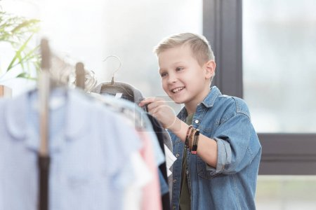 smiling boy holding hanger with cloth in hand at shop