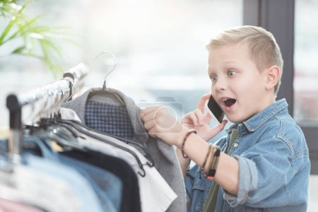 Photo for Surprised boy using smartphone while holding cloth in hand at shop - Royalty Free Image