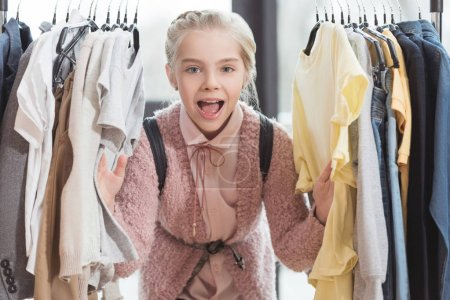 smiling child looking at camera surrounded by clothes on hanger at store