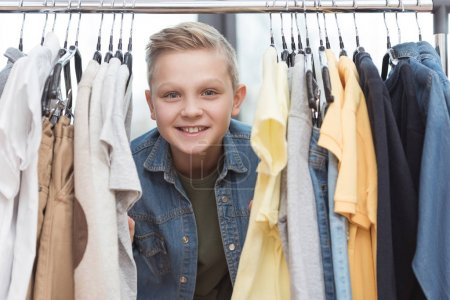 smiling boy looking at camera surrounded by clothes on hanger at store