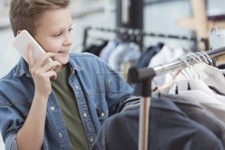 Photo for Smiling boy using smartphone while holding cloth in hand at shop - Royalty Free Image