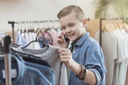 smiling boy using smartphone while holding cloth in hand at shop