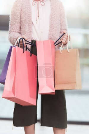 cropped image of  child holding colored paper bags at shop