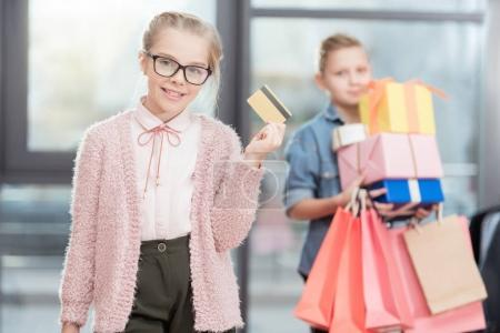 kid in glasses holding credit card in hand with boy holding boxes on background