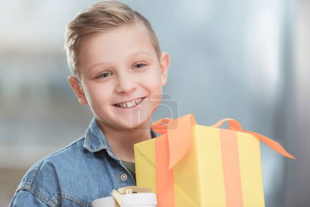 smiling boy holding stacked boxes at shop