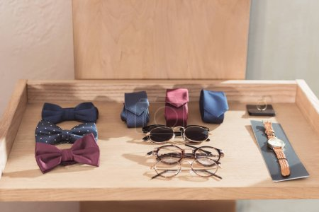 Photo for Bow ties, neckties, glasses and wristwatch laying on wooden display at shop - Royalty Free Image