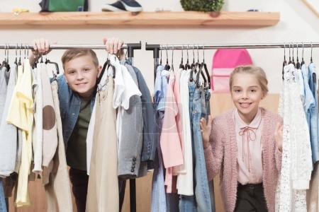 Photo for Two smiling kids looking at camera while standing under cloth hanger at shop - Royalty Free Image