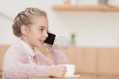 smiling child sitting with cup in hands and using smartphone