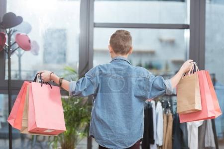 Photo pour Vue arrière du garçon avec des sacs à provisions en papier dans les mains au magasin - image libre de droit
