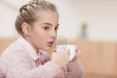adorable child blowing on coffee in cup while sitting at cafe