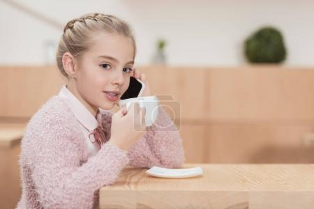 adorable kid sitting at cafe and speaking on smartphone while drinking coffee at cafe