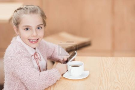 smiling child sitting at table with smartphone in hands