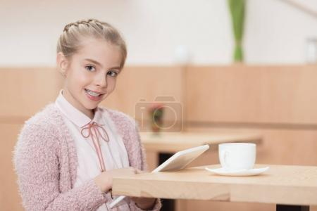 smiling child with digital tablet looking at camera while sitting at table