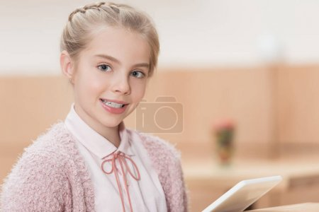 smiling child with digital tablet looking at camera at cafe