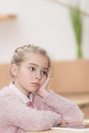 bored child sitting at table with digital tablet and looking away